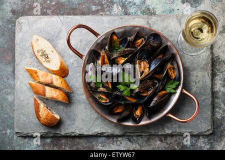 Mussels in copper cooking dish and French Baguette with herbs on stone slate background - Stock Photo