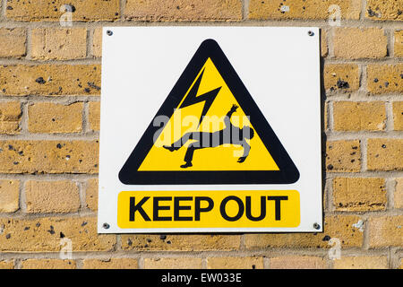 Industrial warning plate in an electricity plant, signaling death danger for high voltage power in the surrounding - Stock Photo