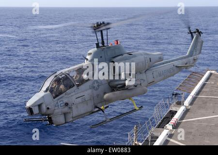 U.S. Marine Corps AH-1W Super Cobra attack helicopter takes off from the flight deck of the amphibious transport - Stock Photo