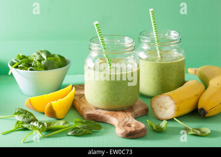 healthy green smoothie with spinach mango banana in glass jars - Stock Photo