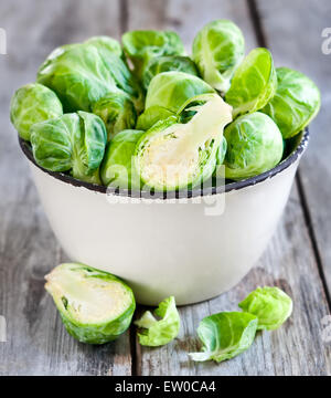 Brussels sprout in small rustic bowl on old wooden table. - Stock Photo