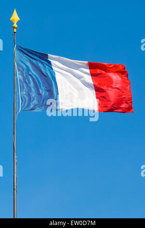 Vertical shot of the flag of France on a pole, waving in the wind during a sunny day with clear blue sky. - Stock Photo