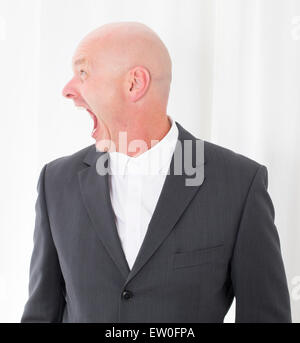 bald-headed man in a suit looking to the side and making a grimace - Stock Photo