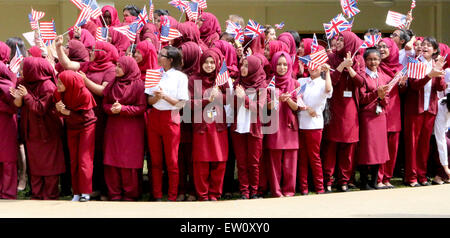 Young muslim students wave flags as they welcome U.S. First Lady Michelle Obama during a visit to the Mulberry School - Stock Photo