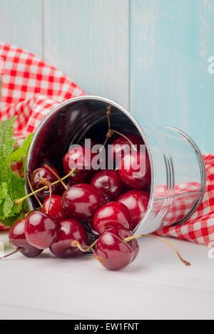 Cherries in small metal bucket on the wooden table. - Stock Photo