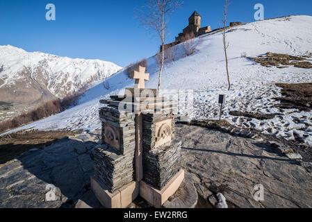 Small stone cross next to Holy Trinity Church (Tsminda Sameba) from 14th century near Gergeti village, Stepantsminda - Stock Photo
