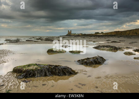 View of seaweed covered rocks and pools on beach at low tide, at sunset, with 12th Century ruined church in distance, - Stock Photo
