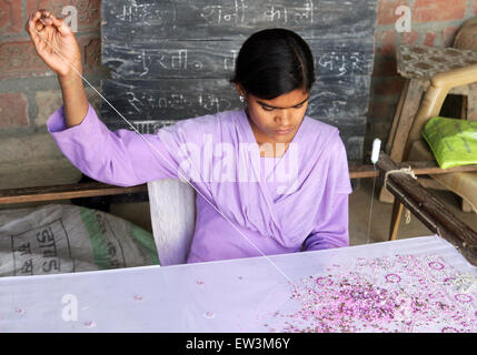 Young woman with embroidery in a village of Rampur region, Uttar Pradesh, India - Stock Photo
