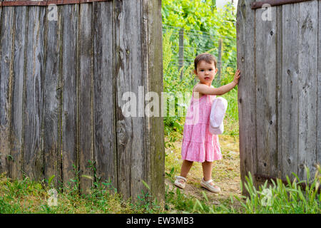 Two year-old toddler girl is  opening wooden wicket gate - Stock Photo