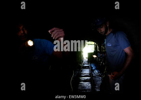 Men illuminating with their headlights inside Galleria Bollico a deserted water mine in Parque Rural de Teno at - Stock Photo