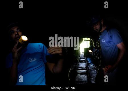 Men illuminating with their headlight in the rock cut Galleria Bollico water mine in Parque Rural de Teno at the - Stock Photo