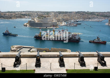 Three tugs ease the Maridive Offshore base out of the Grand Harbour in Valletta Malta passing the saluting battery. - Stock Photo