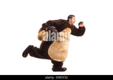 Studio shot of a horrified man in a bear costume running away from something isolated on white background - Stock Photo