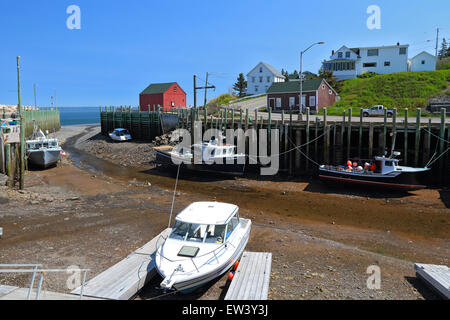 Bay of Fundy, Nova Scotia, Canada. Hall's Harbour fishing village at low tide with fishing boats on mud. Halls Harbor. - Stock Photo