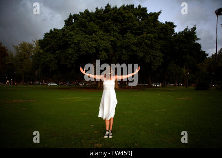 A woman dressed in a white dress stands in front of a Banyan Tree in Honolulu Hawaii. - Stock Photo