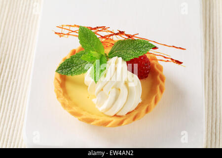 Custard tart topped with cream and raspberry - Stock Photo