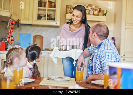 Family of four gathered in the kitchen for dinner - Stock Photo