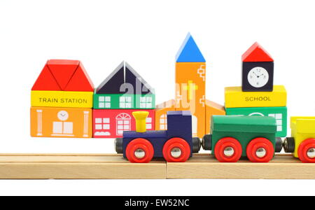 Wooden train on the railroad and houses made of toy blocks  isolated over white - Stock Photo