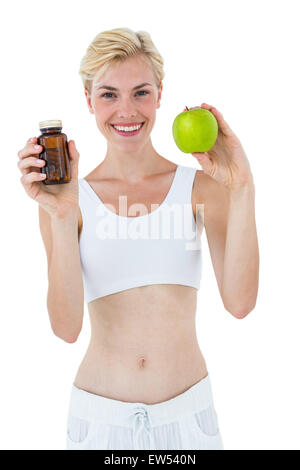 Fit blonde woman holding medicine and green apple - Stock Photo
