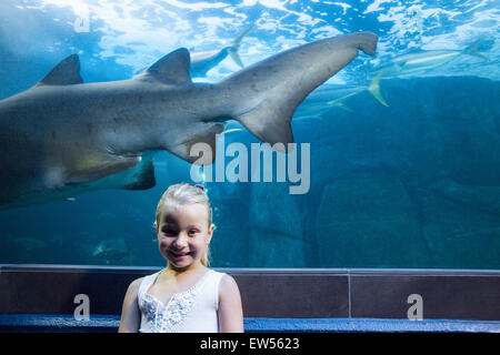 Young woman behind a shark tank looking at camera - Stock Photo