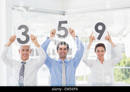 Smiling business team showing paper with rating - Stock Photo