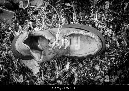 old shoe washed up on the shore - Stock Photo