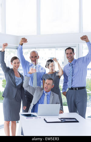 Smiling business team celebrating and looking at camera - Stock Photo