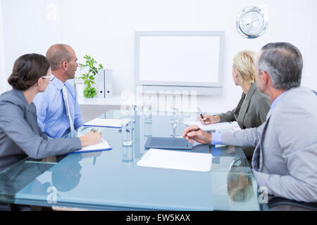Business team looking at time clock - Stock Photo