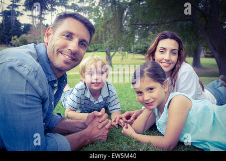 Happy family in the park lying down together - Stock Photo