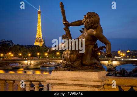 Twilight over statue on Pont Alexandre III with River Seine and Eiffel Tower beyond, Paris, France - Stock Photo