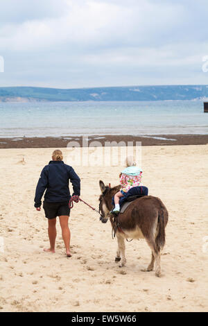 Young girl enjoying donkey ride on the beach at Weymouth, Dorset in June - Stock Photo