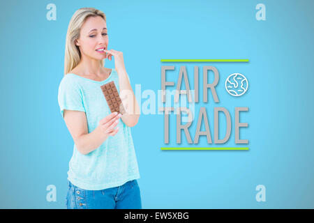 Composite image of pretty blonde feeling guilty to eat bar of chocolate - Stock Photo