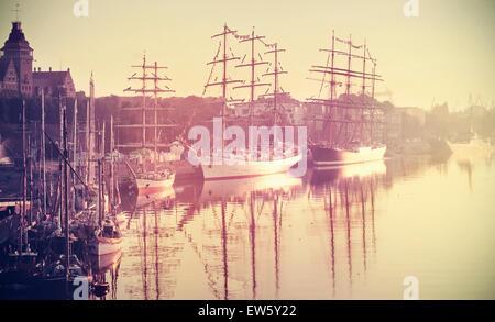 Retro toned photo of sailing ships at sunrise, Szczecin in Poland. - Stock Photo