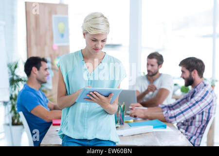 Businesswoman using tablet in the office - Stock Photo