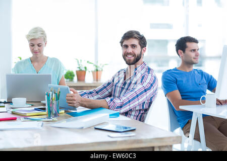 Businessman holding a tablet in the office - Stock Photo