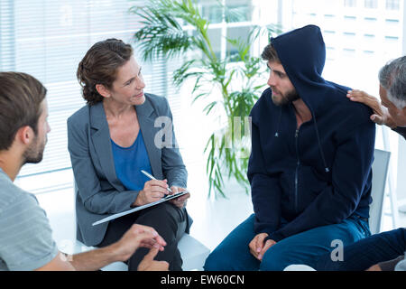 Concerned man comforting another in rehab group - Stock Photo