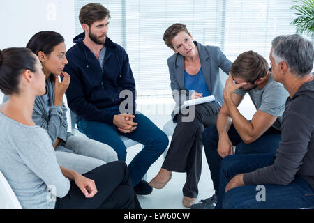Concerned woman comforting another in rehab group - Stock Photo