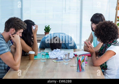 Exhausted creative business team in meeting - Stock Photo