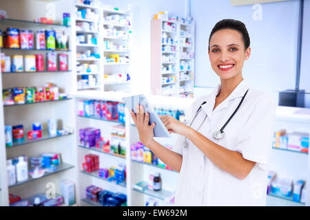 Composite image of pretty nurse using tablet pc - Stock Photo