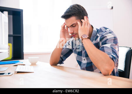Pensive businessman sitting at the table in office - Stock Photo