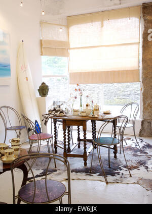 Metal chairs at Jacobean style table in coastal dining room with rough linen blinds and a vintage cow hide rug - Stock Photo