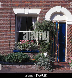 Exterior of a small townhouse with pink geraniums in the window box and a canvas curtain on the front door - Stock Photo