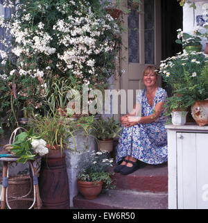 Portrait of smiling woman sitting on steps outside front door - Stock Photo