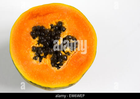 Papaya, Carica papaya, and seeds, cut in half on a white background with copyspace - Stock Photo