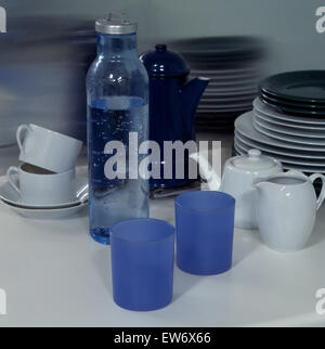 Close-up of blue plastic beakers with white cups and teapot and a bottle of water - Stock Photo