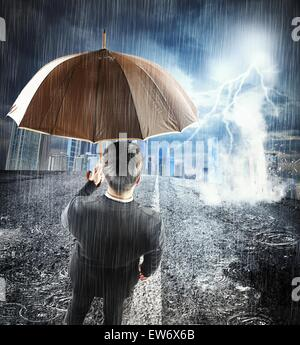 Businessman sheltering from problem - Stock Photo