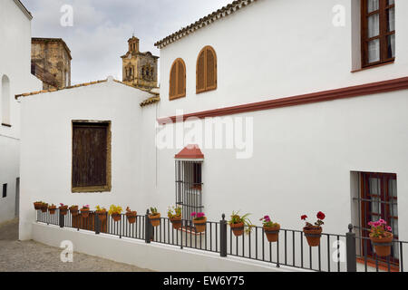Church of Saint Peter belfry with whitewashed houses and flowerpots in Arcos de la Frontera Spain - Stock Photo