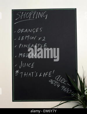 Close-up of a shopping list written on a blackboard noticeboard - Stock Photo