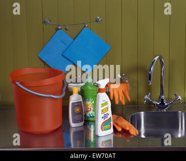 Close-up of cleaning products with an orange plastic bucket and rubber gloves - Stock Photo