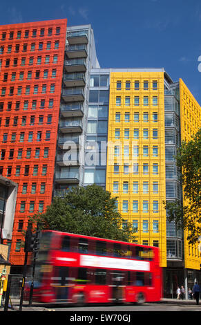 Red London double decker bus passing by brightly colored office blocks - Stock Photo